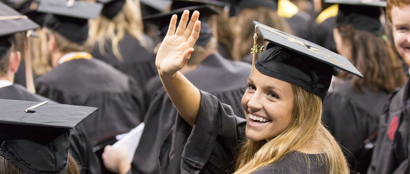 Graduate in cap and gown waves to her friends