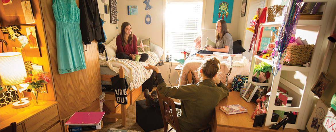 Three female students sitting in a dorm room, with two on twin beds and one at a student desk, with a lot of decor items like wall posters, school supplies, clothing hanging on a closet door, and other typical dorm decor