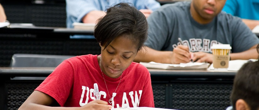 Female student wearing a red T-shirt that reads USC Law takes notes at a desk in a law school classroom