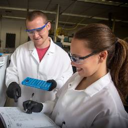 Male and female students in white lab coats and safety glasses, holding lab equipment and recording data in a logbook