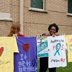 Two female students hang newly decorated T-shirts to dry on a clothesline outdoors, with messages in support of health-related issues