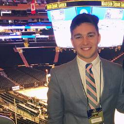 Male student in suit and tie with ID badge on a lanyard, standing in Madison Square Garden arena with Jumbotron in background