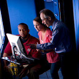 Professor pointing to computer screen, explaining something to a male and a female student who are gazing at the screen