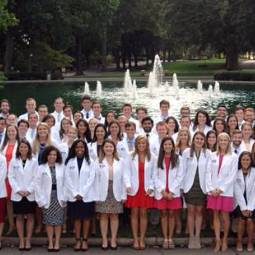Group of 50 or more students in white lab coats posing for a group shot outdoors in front of a fountain