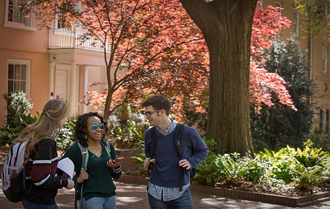Image: Three students on Horseshoe with colorful leaves
