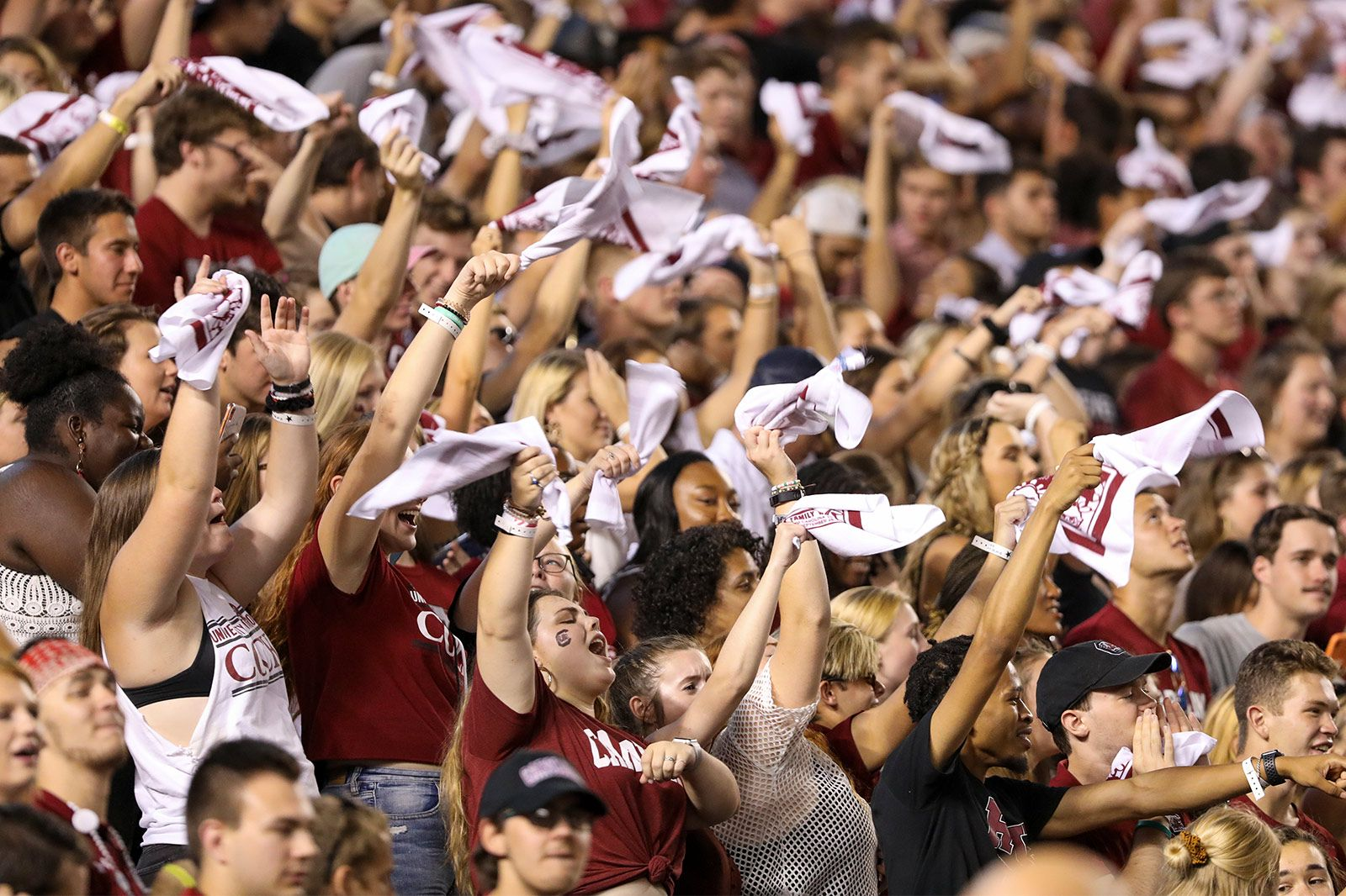 Large crowd of Gamecock students cheering in the stands at Williams Brice Stadium with arms raised, twirling towels in the air.