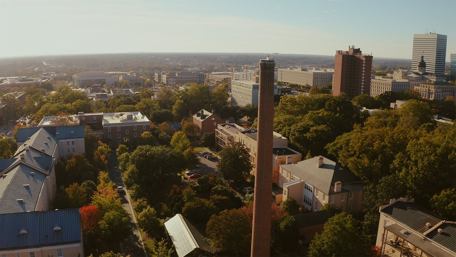 Aerial view of campus with rooftops, trees the smokestack in foreground and city of Columbia skyline off in the distance.