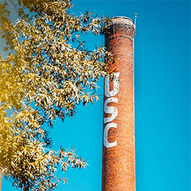 The smokestack with the letters USC on it framed by tree limbs in front of a blue sky.