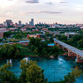 Drone photo of the Gervais Street bridge over the Congaree river going into Columbia with the skyline in the background.