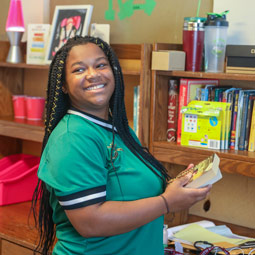 Student putting books away in her new room.