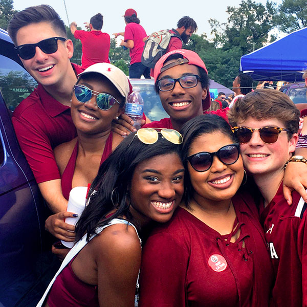 Students gathered together smiling at the camera wearing garnet and black gamecock gear at a tailgate.