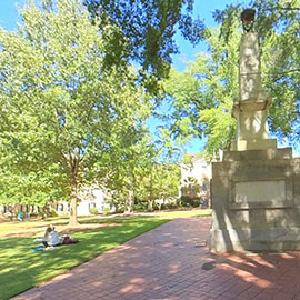 beautiful green space of the Historic Horseshoe with the Maxcy Monument and students hanging out on a blanket in the grass.