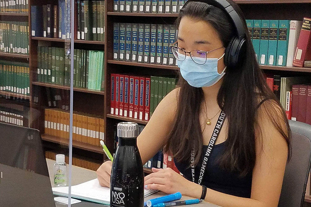 a student sitting in the library wearing a face covering