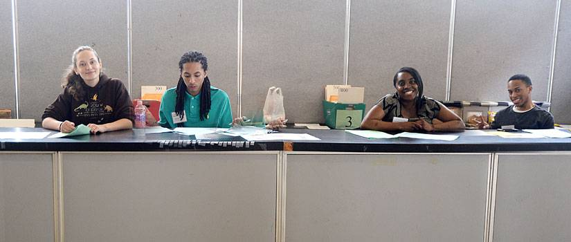 Four students sitting behind a check-in table at an event