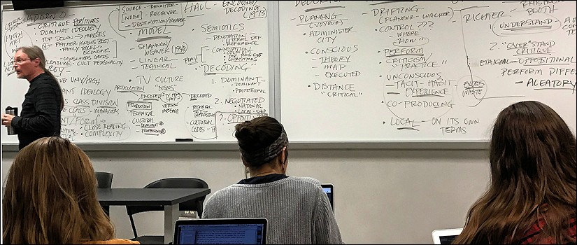 Professors Byron Hawk teaching with a very busy whiteboard behind him