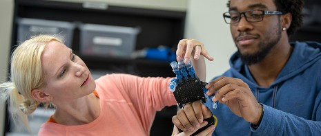 A professor and student experiment with a robotic hand