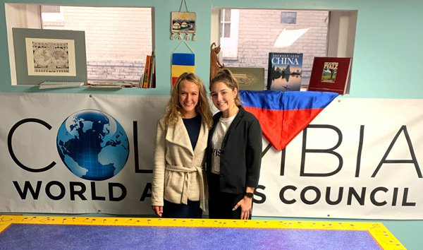 Lilly Kays and a fellow intern stand in front of a Columbia World Affairs Council sign.