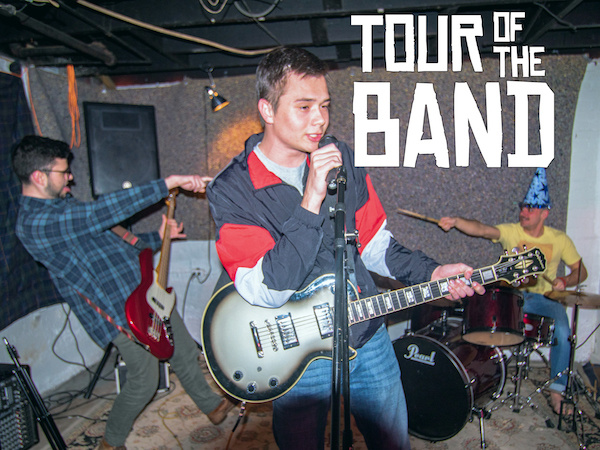 Promotional image of Tour of the Band. The band members are playing guitar, bass, and drums.