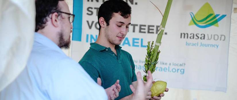 Young man standing holding a large fruit