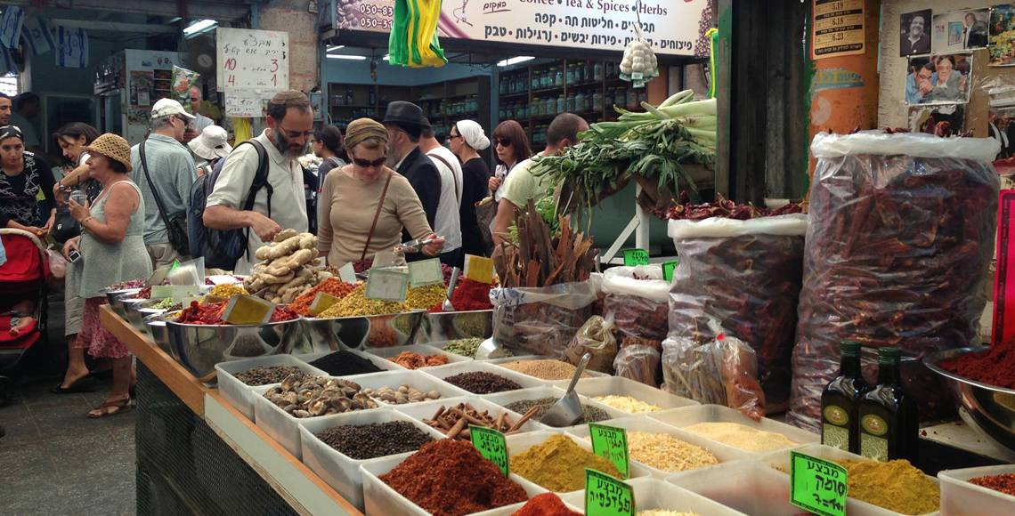 Two people peer over the selection at an outdoor spice market