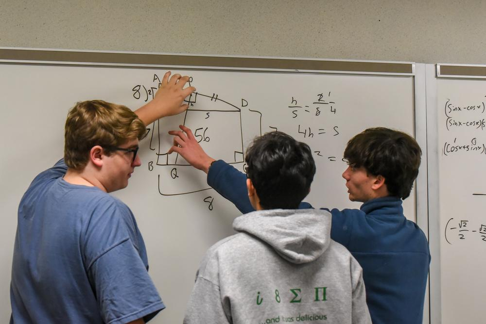 Students working a math problem at a whiteboard