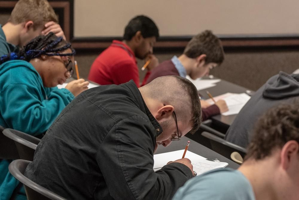 Students taking a written test with pencil and paper