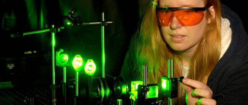 Female student in front of a green laser set up.