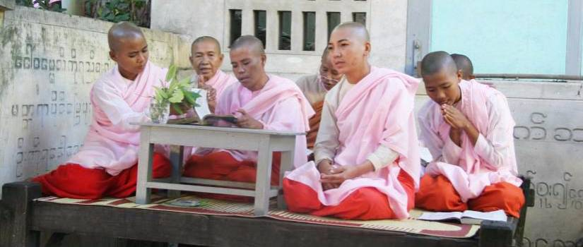 people wearing pink and red robes sharing a book