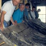 Fitting exterior plank to frames to begin process of reattaching timber to the extant hull. (SCIAA photo)