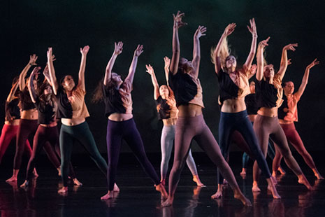 Click to view video.  Shown: Group of dancers with arms raised in Fall 2019 Student Choreography Showcase