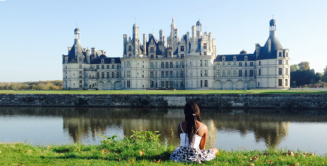 A student sits near a large château in France.