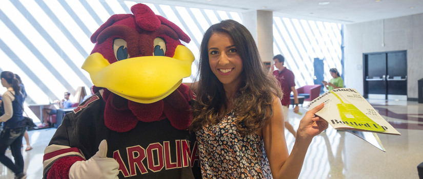 A student poses with the Gamecocks mascot, Cocky.