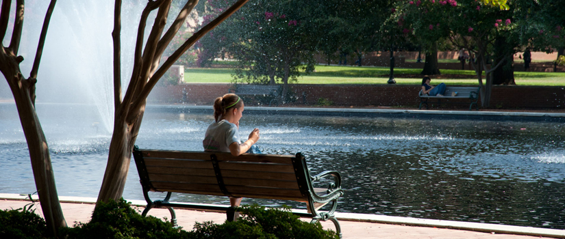 Student sitting on a bench in front of a fountain