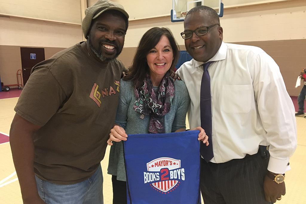 Melanie Huggins with storyteller Darion McLoud and Mayor Steve Benjamin.
