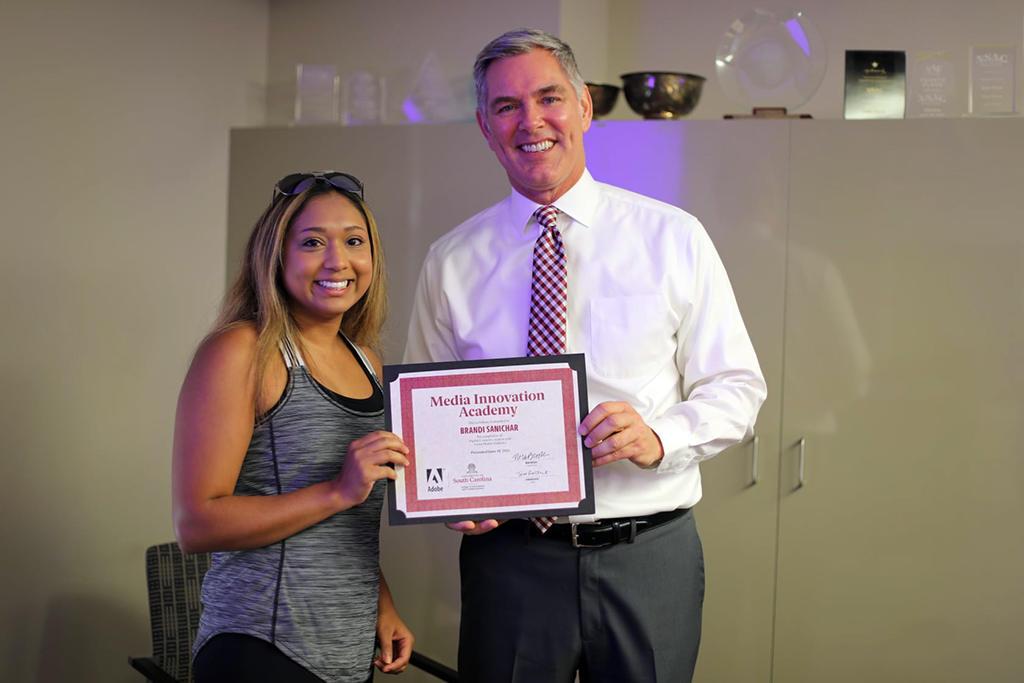 Dean Tom Reichert presenting an MIA certificate of completion to Brandi Sanichar.