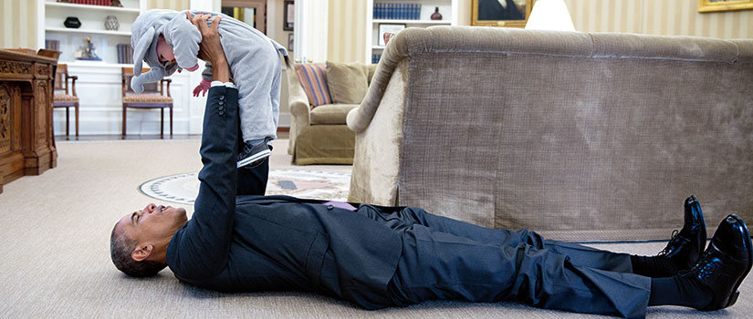 A photo that Pete Souza took of President Obama in the Oval Office. Obama is lying on the floor holding a baby up.