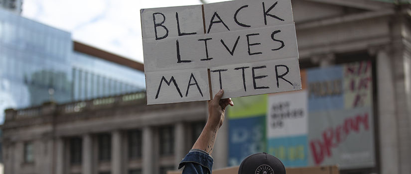 Black Lives matter sign being held up at a protest event