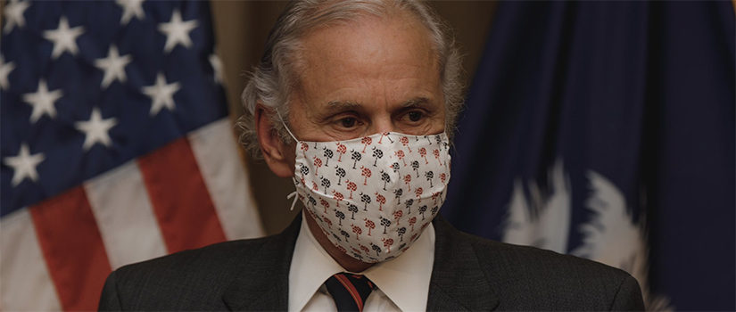 Governor Henry McMaster wearing a mask while speaking at a podium