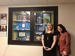Ashley Quam and Jennifer Morrison pose in front of the display.