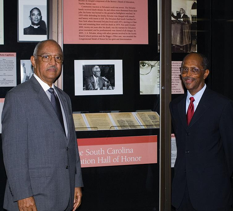 J. A. De Laine, Jr. and B. B. De Laine standing in front of the Hall of Honor exhibition of their father, J. A. De Laine (1898-1974), schoolteacher, civil rights leader, community leader who led the efforts to file the Briggs v. Elliott case.
