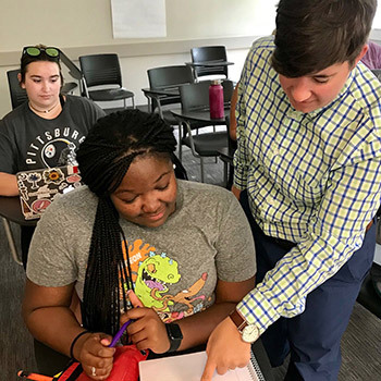 College of Education faculty member Kate Ascetta shows an African American student something in a notebook while a white student works on a laptop in the background.