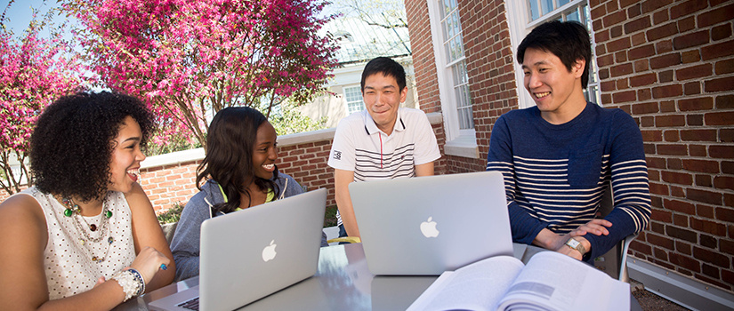 several diverse students sitting outside with computers