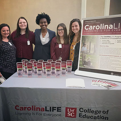 smiling women with CarolinaLIFE pamplets and sign