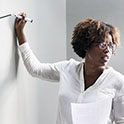 african american woman writing on whiteboard
