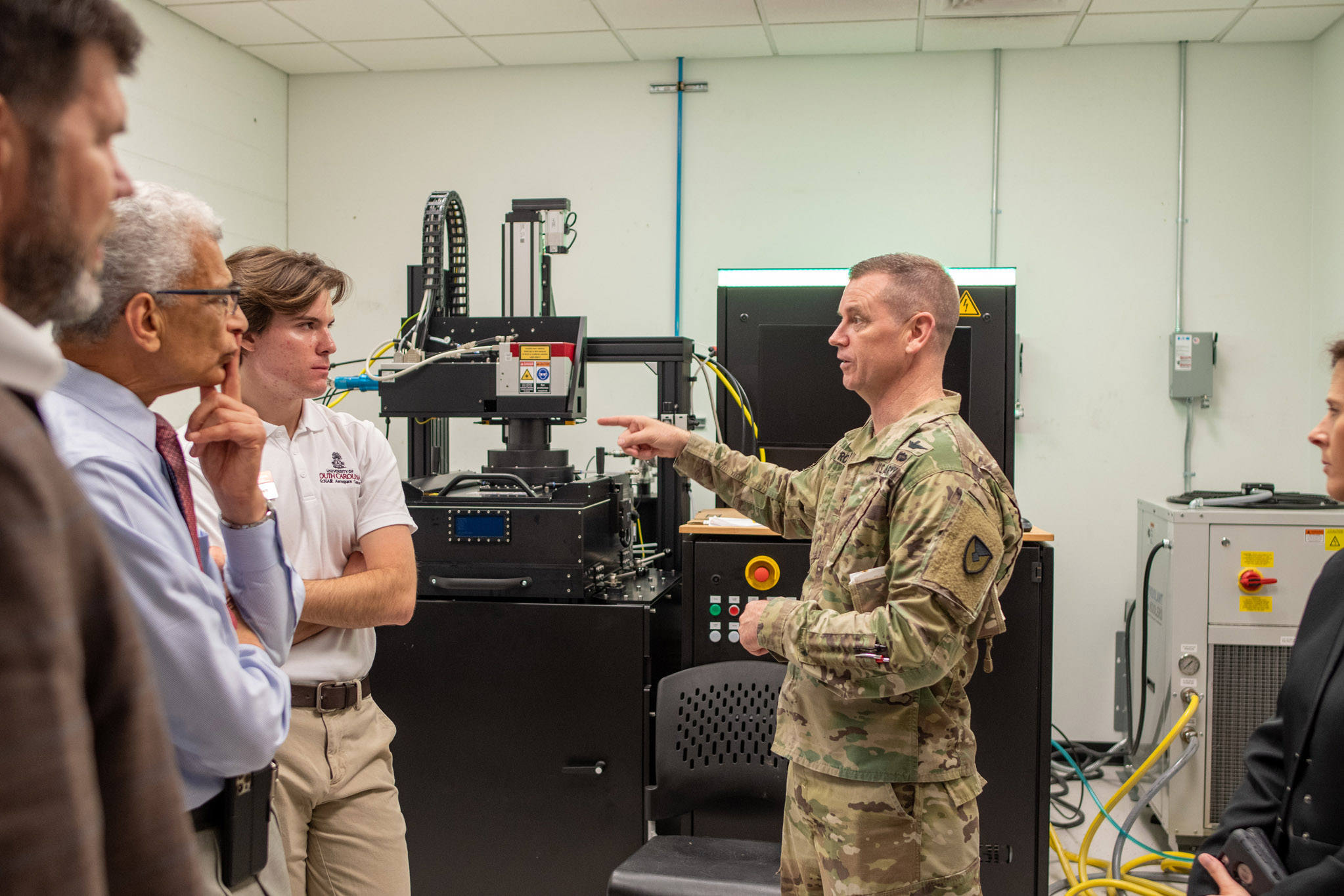 MCOM Commander Maj. Gen. Todd Royar talking with a student and Dr. Bayoumi in a lab space.