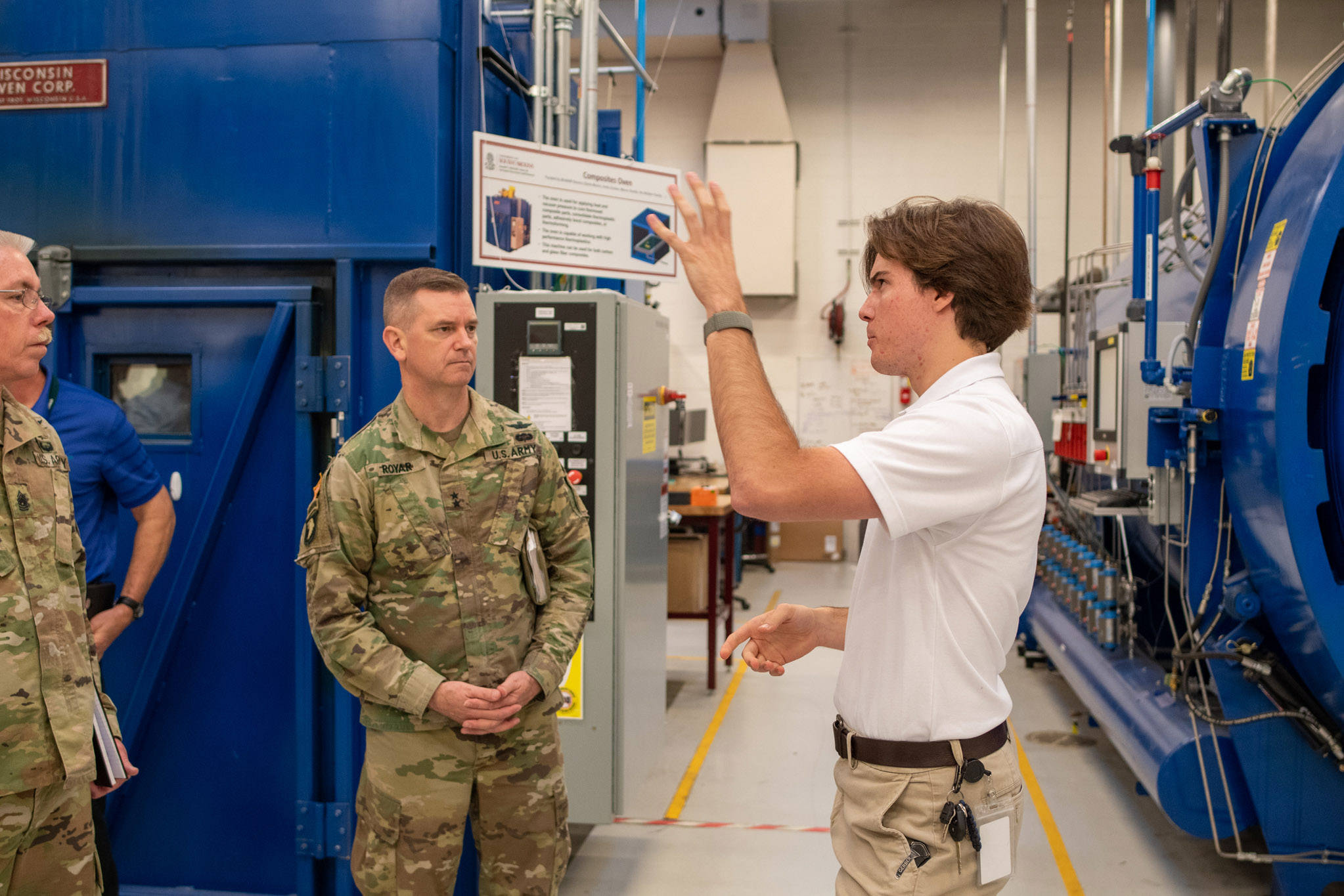 A student talks to Sarj. Maj. George Dove and AMCOM Commander Maj. Gen. Todd Royar as he is giving them a tour through the McNair Center. Large industrial equipment is in the background.