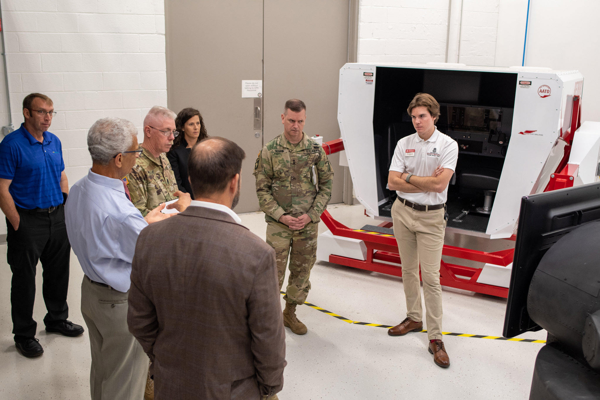 Dr. Bayoumi talks to army officials and student in front of technology.