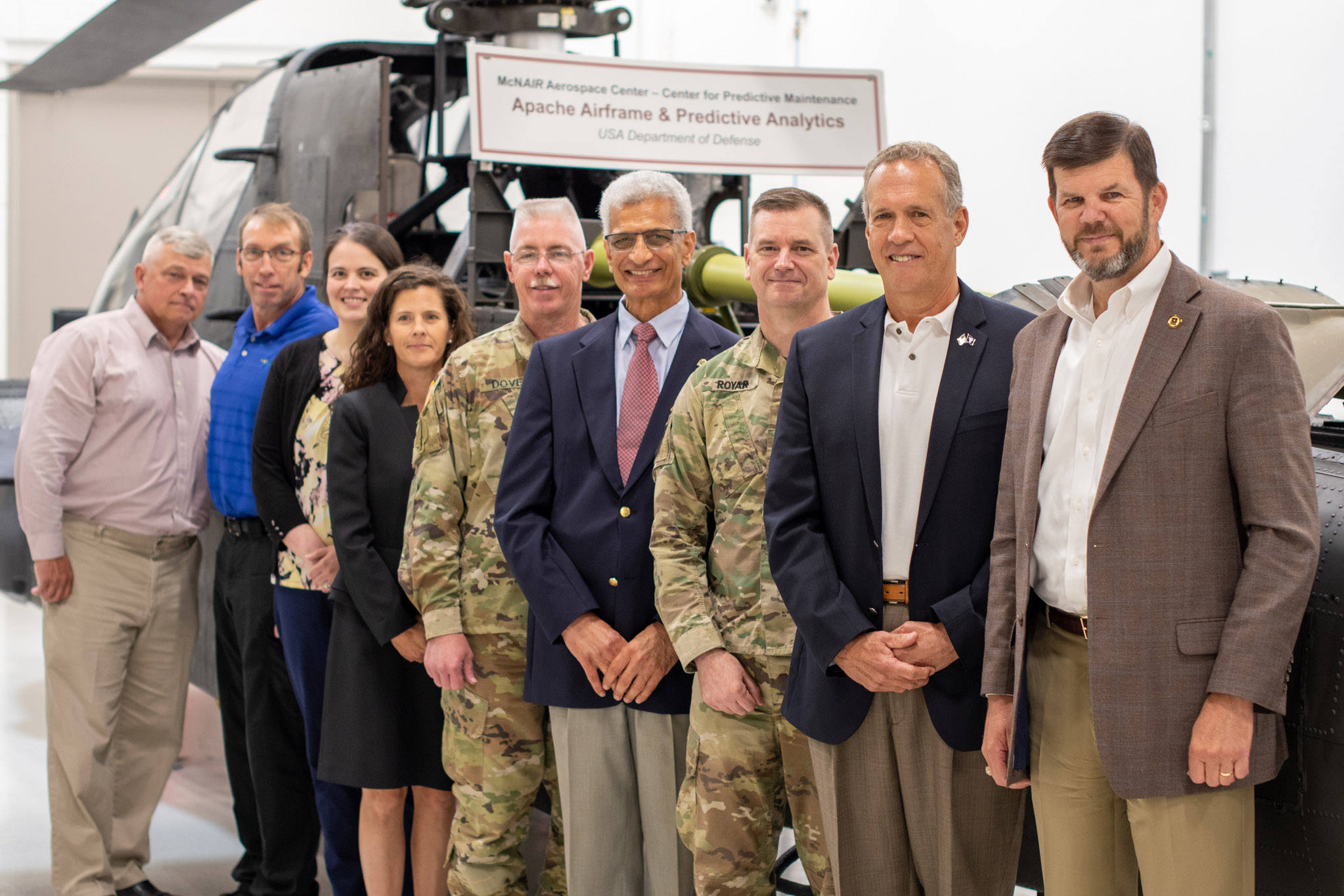University of South Carolina faculty, staff and Army officials stand in front of an Apache Airframe in the McNair Center.