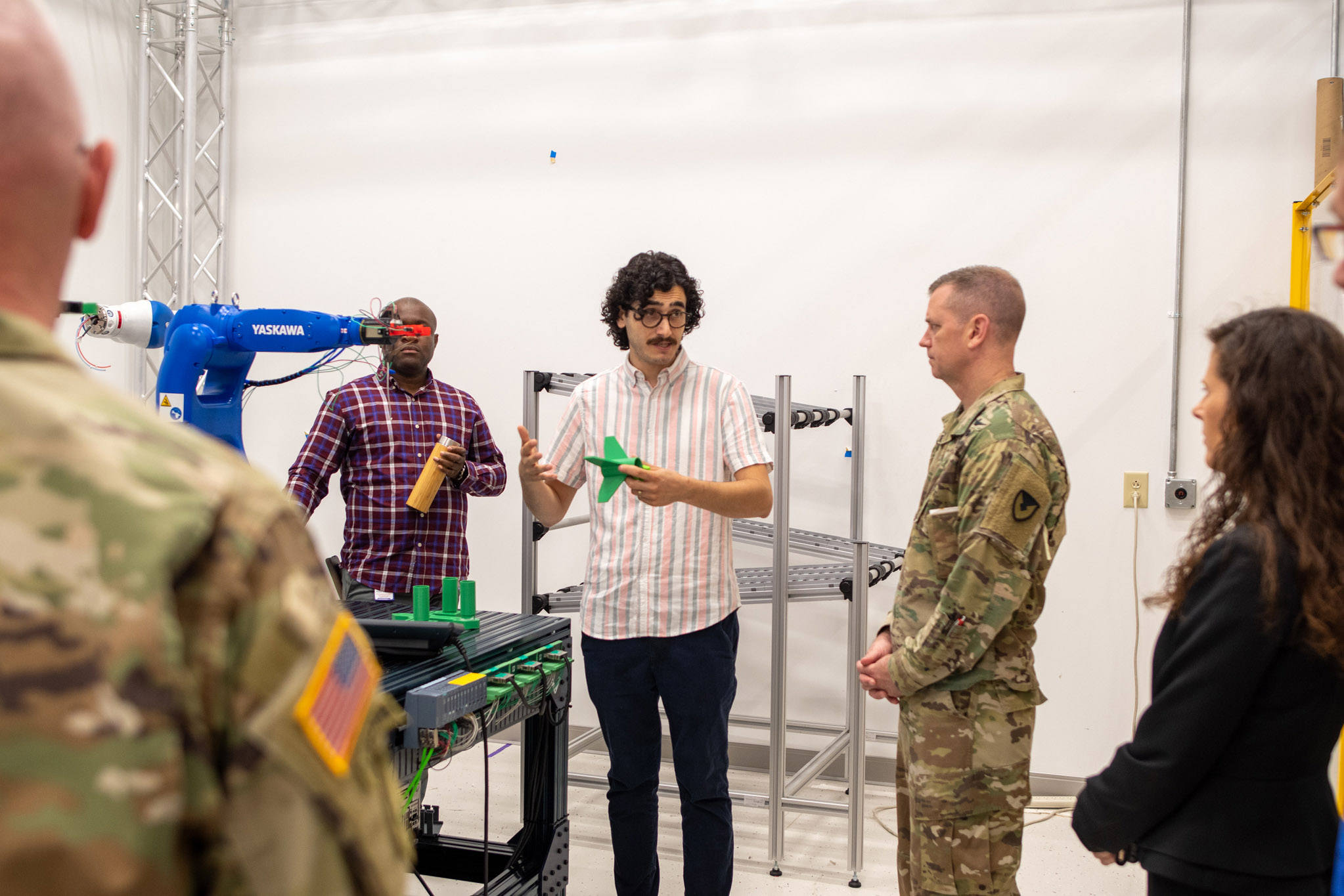 a professor is presenting to Army officials standing next to a robotic arm.