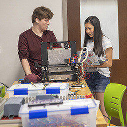 two students talk next to a 3D printer